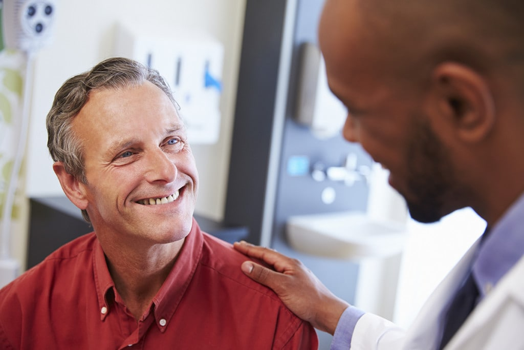 Male Patient Being Reassured By LASIK surgeon