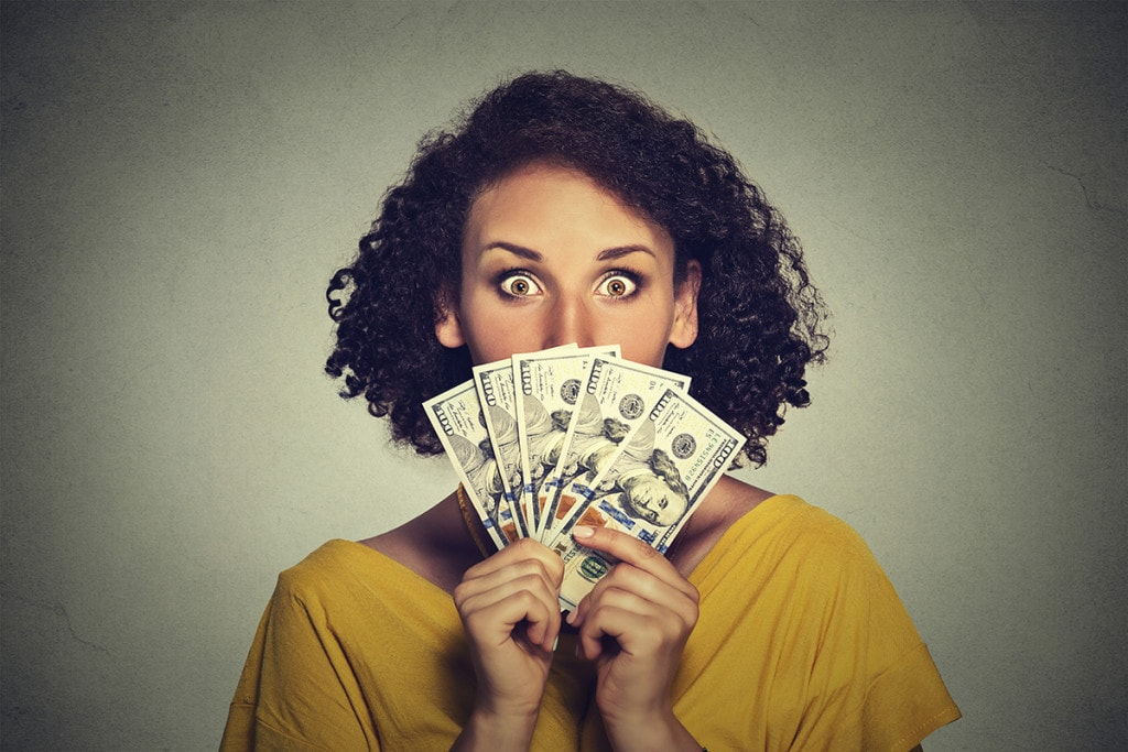 Woman evaluating LASIK price looking through a fan of dollar banknotes