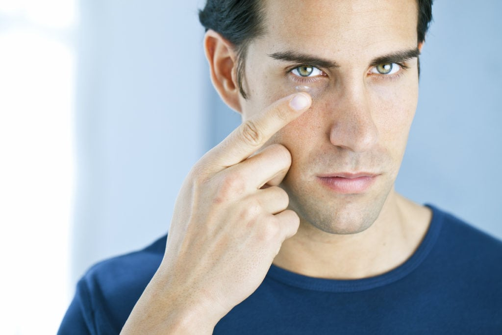 man putting in contact lens and dealing with contact lens problems